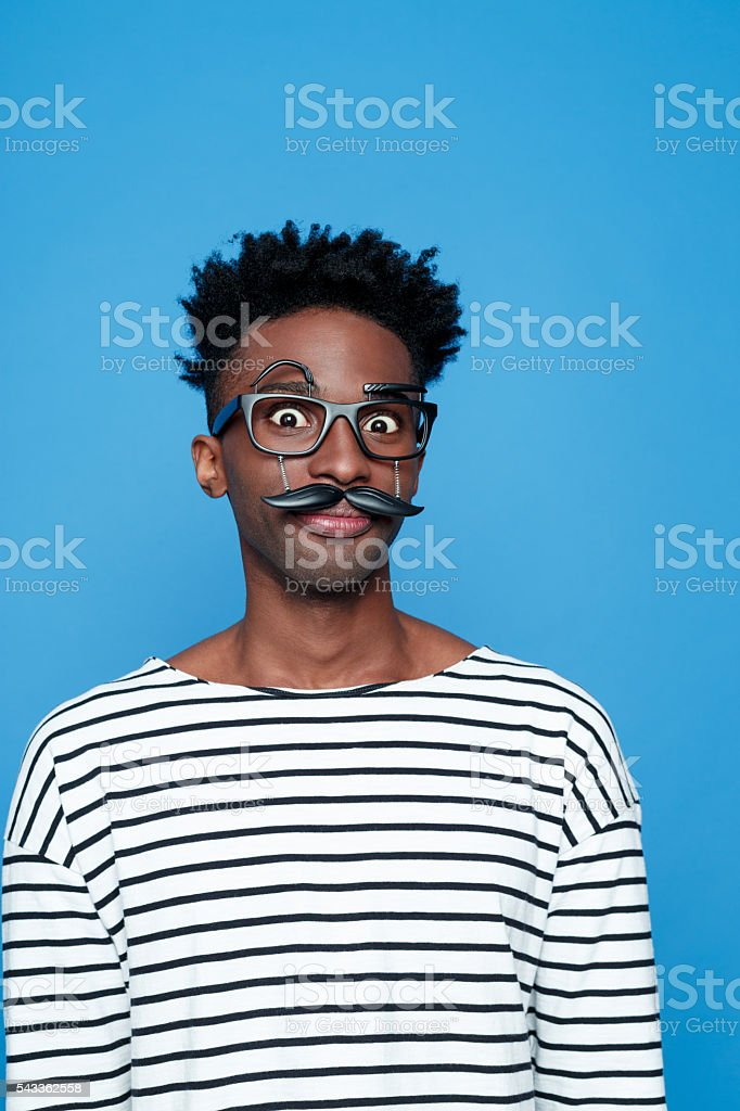 Surprised afro american young man wearing funny glasses Portrait of surprised afro american guy wearing striped long sleeved t-shirt and funny glasses, staring at the camera. Studio shot, blue background.  Adult Stock Photo