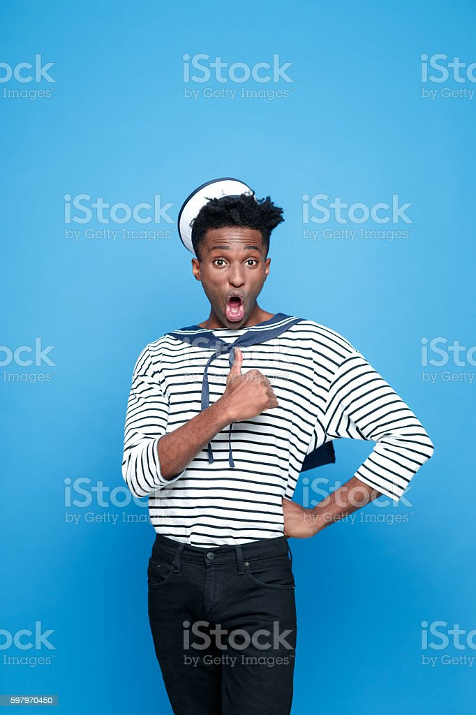 Surprised afro american young sailor Portrait of surprised afro american young man in sailor style outfit, looking at camera withe thumb up and mouth open. Studio portrait, blue background. Adult Stock Photo