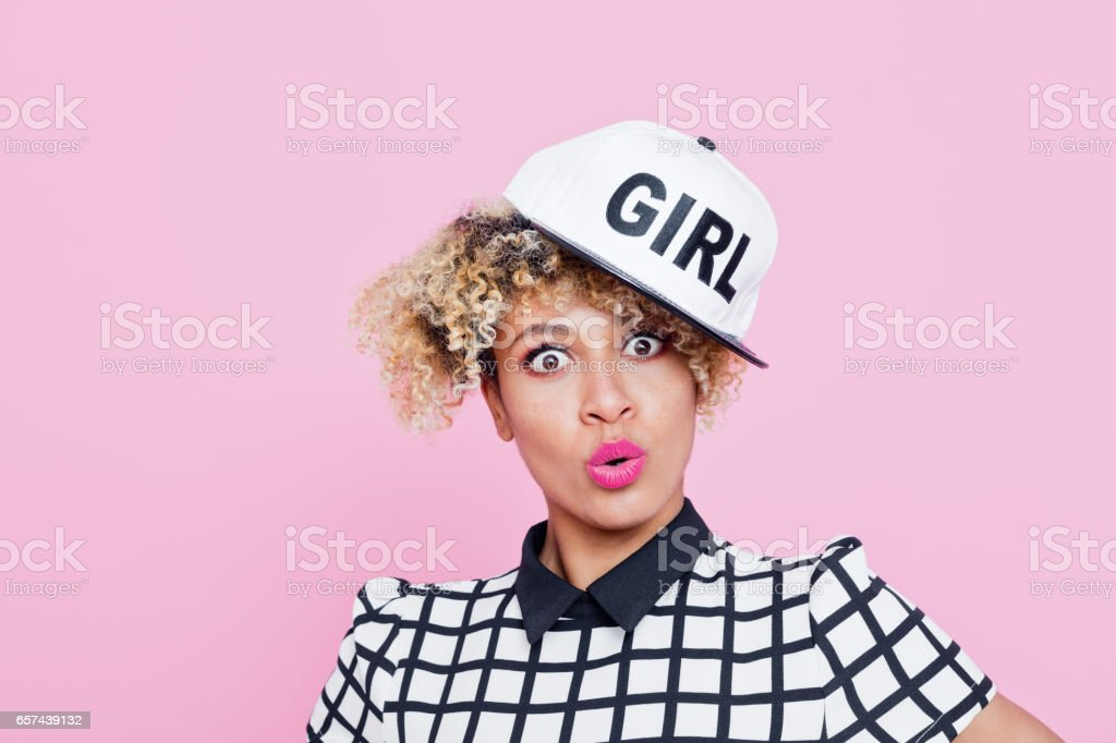 """Surprised afro american young woman wearing baseball cap Studio portrait of surprised afro american young woman wearing baseball cap with text """"girl"""". Pink background. 20-24 Years Stock Photo"""