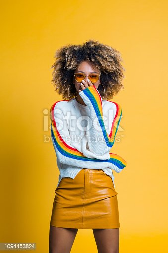 521083232istockphoto Surprised afro girl standing against yellow background 1094453824