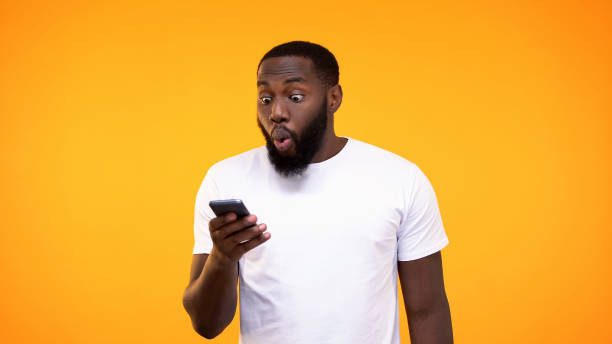 Surprised afro-american guy looking at phone screen, lottery winner, betting app Surprised afro-american guy looking at phone screen, lottery winner, betting app aghast stock pictures, royalty-free photos & images