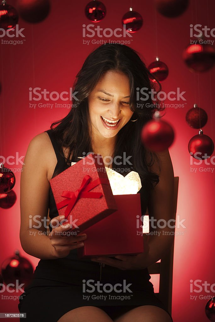 Surprised and Laughing Hispanic Model Opening Magical Christmas Gift stock photo