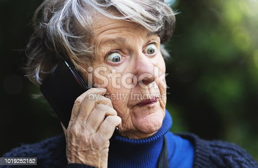 A senior woman listening to her mobile phone outdoors looks utterly horrified and shocked by what she hears.