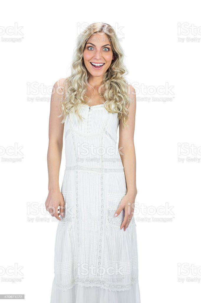 Surprised attractive model in white dress posing stock photo