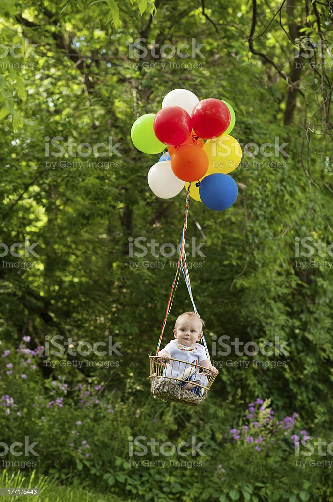 Surprised Baby Flying Away with Balloons royalty-free stock photo