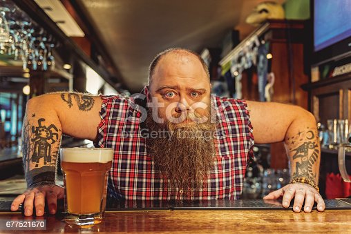 istock Surprised bearded male working in pub 677521670