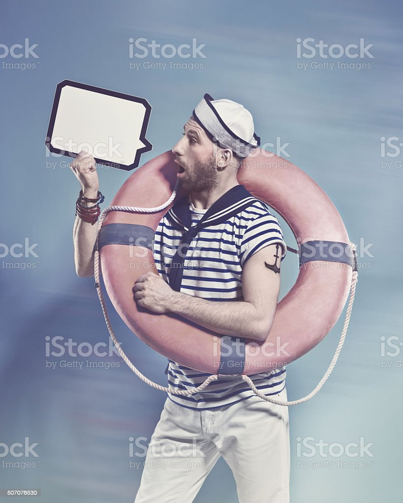Surprised bearded sailor holding lifebuoy and speech bubble Side view of bearded sailor man wearing white and blue striped t-shirt and sailor hat, holding lifebuoy on shoulder and speech bubble in hand. Standing against blue background. Studio shot, one person.  Adult Stock Photo