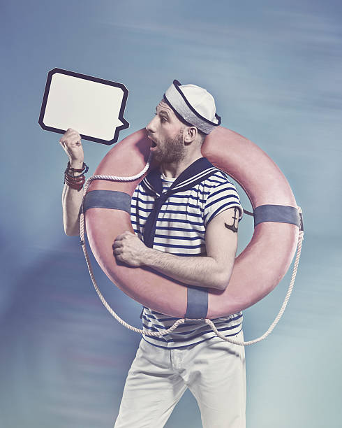 Surprised bearded sailor holding lifebuoy and speech bubble Side view of bearded sailor man wearing white and blue striped t-shirt and sailor hat, holding lifebuoy on shoulder and speech bubble in hand. Standing against blue background. Studio shot, one person.  sailor suit stock pictures, royalty-free photos & images