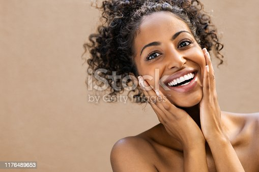 Beautiful young woman smiling after fantastic face treatment . Happy beauty african girl with curly hair and toothy smile excited after spa treatment isolated on background with copy space. Surpise and astonishment beauty concept.