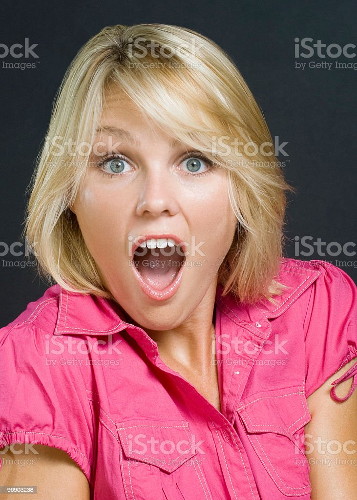 Surprised beautiful young blonde woman in pink royalty-free stock photo