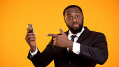 istock Surprised black businessman pointing on smartphone, cool business app, shopping 1152598004