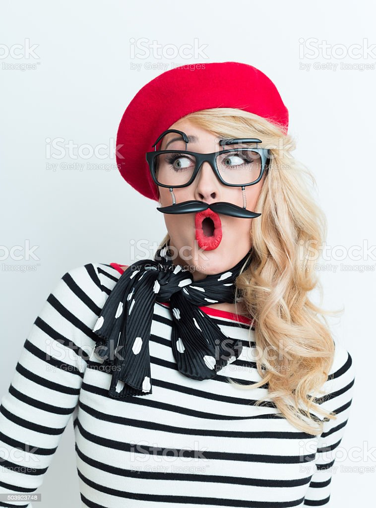 Surprised blonde french woman wearing red beret and facial mask Portrait of surprised blonde woman in french outfit, wearing a red beret, striped blouse, neckerchief and funny facial mask. Adult Stock Photo