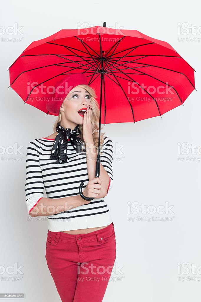 Surprised blonde french woman wearing red beret, holding an umbrella Portrait of surprised beautiful blonde woman in french outfit, wearing a red beret, striped blouse and neckerchief, holding a red umbrella, looking up with hand on mouth. Adult Stock Photo