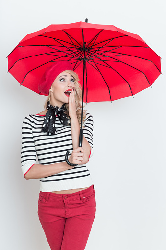 Surprised Blonde French Woman Wearing Red Beret Holding An Umbrella Stock Photo - Download Image Now