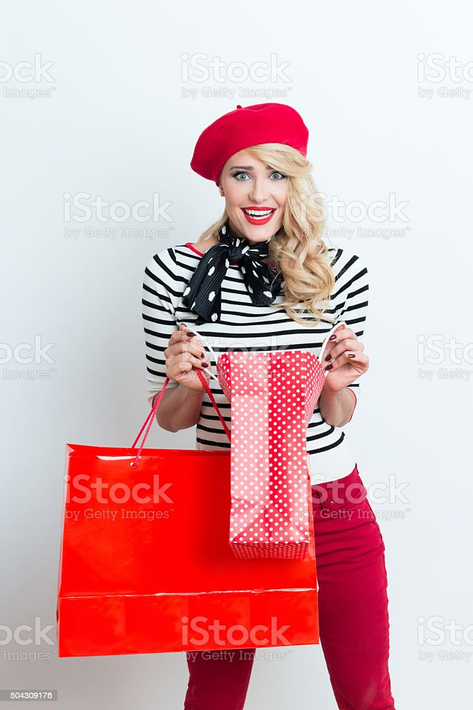 Surprised blonde french woman wearing red beret, holding shopping bags Portrait of surprised beautiful blonde woman in french outfit, wearing a red beret, striped blouse and neckerchief, holding shopping bags, staring at camera. Adult Stock Photo
