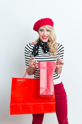 Surprised Blonde French Woman Wearing Red Beret Holding Shopping Bags Stock Photo - Download Image Now