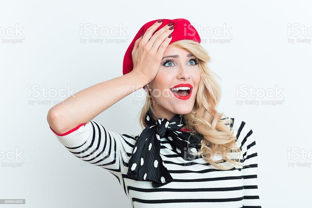Surprised blonde french woman wearing red beret Portrait of surprised beautiful blonde woman in french outfit, wearing a red beret, striped blouse and neckerchief, looking away with hand on forehead. Adult Stock Photo