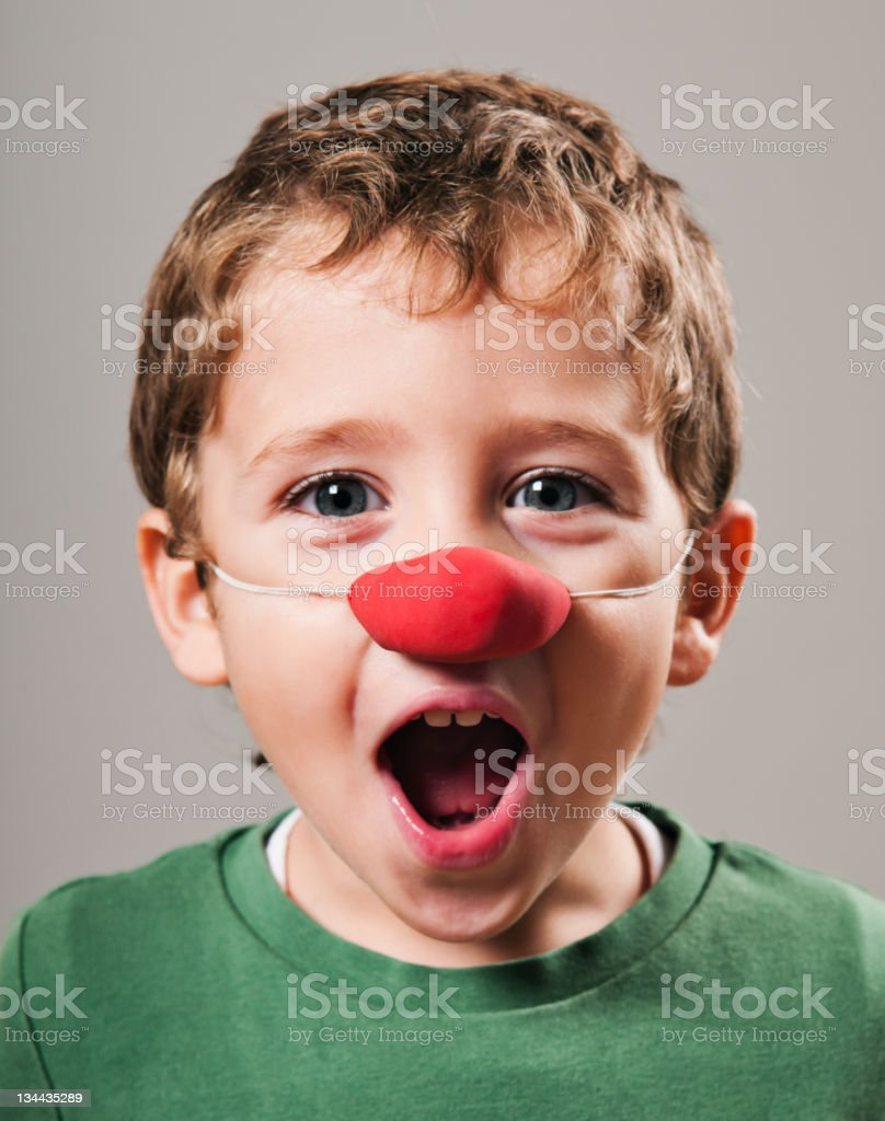 Surprised blonde kid with clown nose royalty-free stock photo