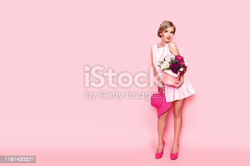 Young blonde woman with a box full of flowers. Horizontal studio shot. Pink background.