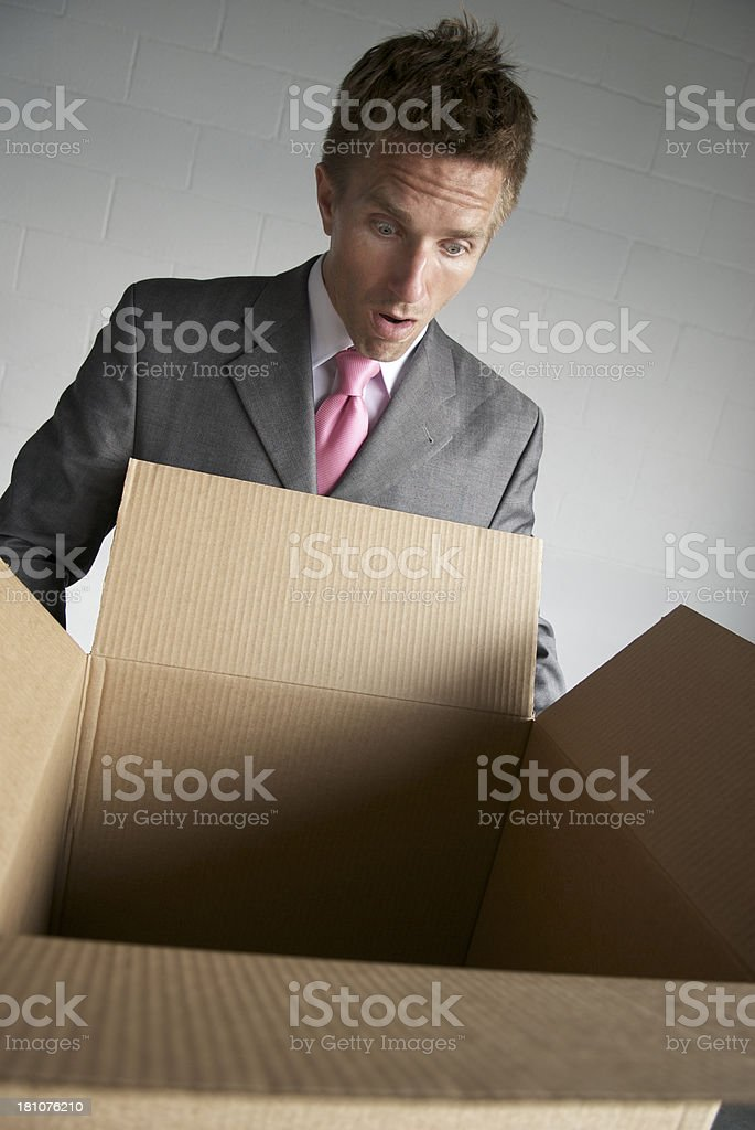 Surprised businessman holds open cardboard box packaging with an...