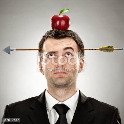 istock surprised businessman red apple on head hit by arrow 157612547