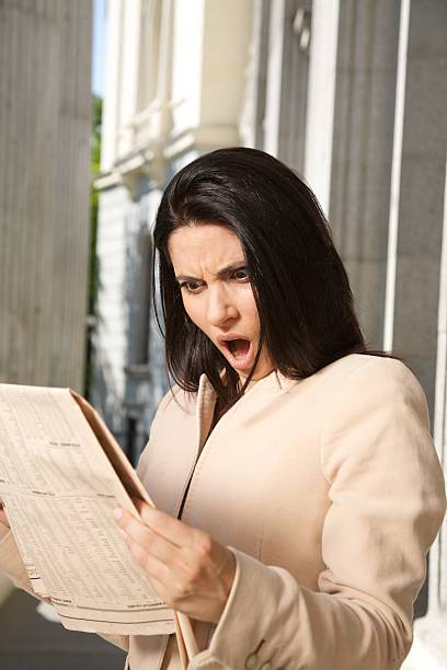 surprised businesswoman reading journal portrait of shocked woman reading financial newspaper. dazzled stock pictures, royalty-free photos & images
