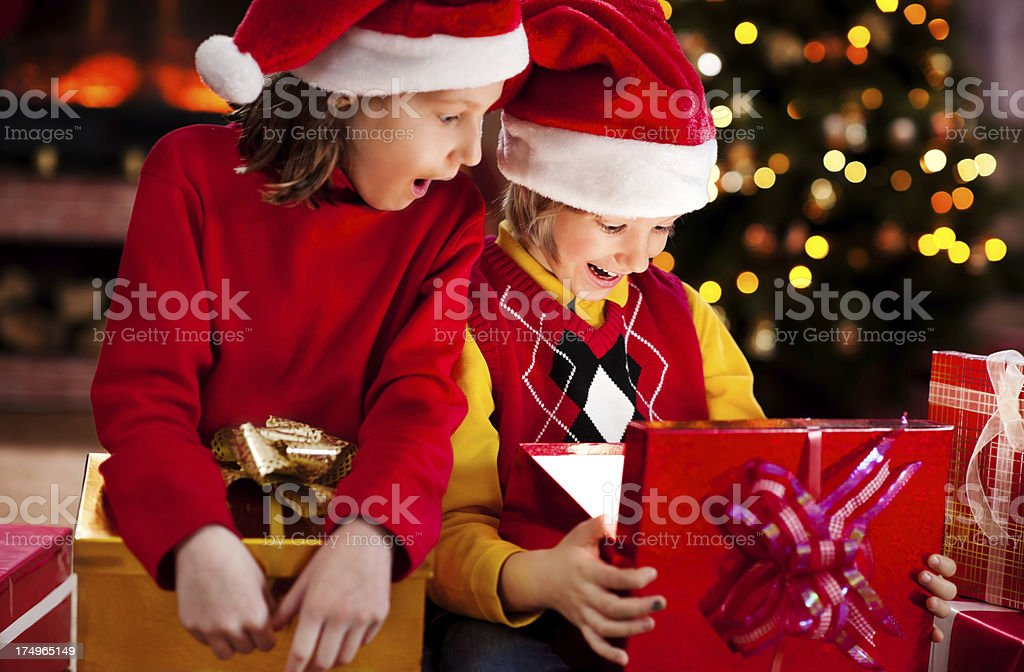 Cute children wearing Santa\'s hats are opening Christmas presents.