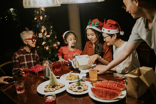 Asian happy family members feel exciting during unwraping Christmas gift box together in Christmas party.