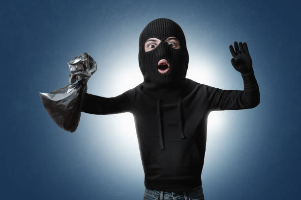 Surprised comic burglar with money bag stopped and take his hands up Surprised comic burglar with money bag stopped and take his hands up bandit stock pictures, royalty-free photos & images