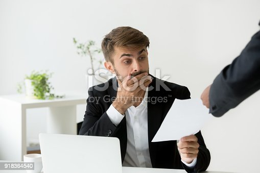 istock Surprised confused caucasian employee receiving dismissal notice from black boss 918364540