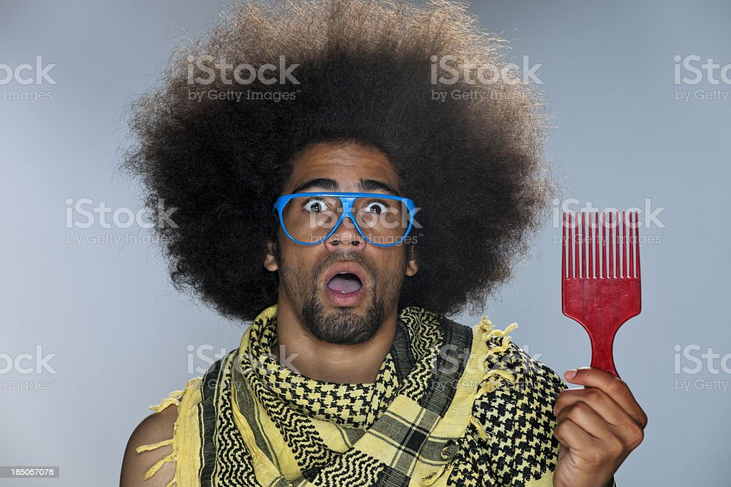 surprised cool black man holding afro hair comb stock photo
