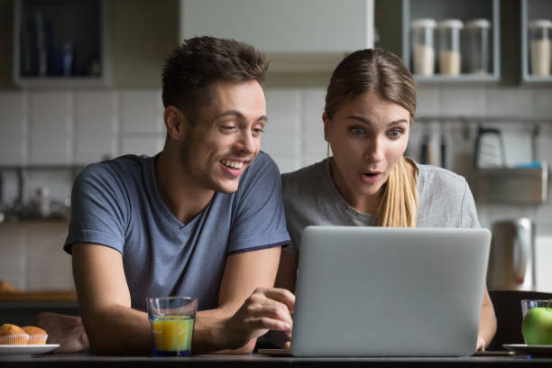 Surprised couple amazed with online shopping sale looking at laptop stock photo