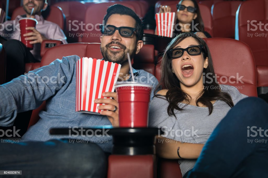 Surprised couple watching a 3d movie stock photo