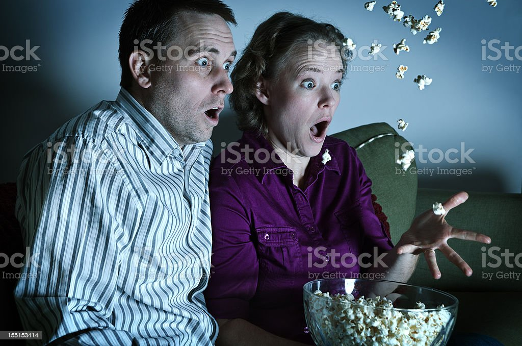 Surprised couple watching a movie at home stock photo