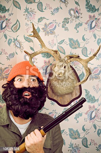 A lumberjack/hunter searches for more unsuspecting fictional animals, a stuffed jackalope (rabbit with antlers) head behind him; vintage retro wall paper background with room for copy space.