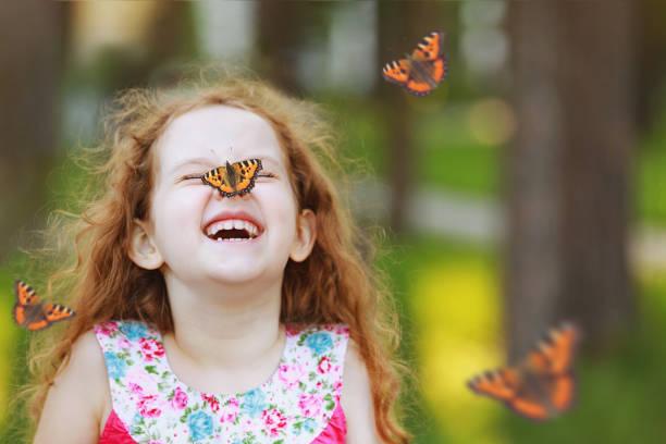 Überrascht lockiges Mädchen mit einem Schmetterling auf seiner Nase. – Foto