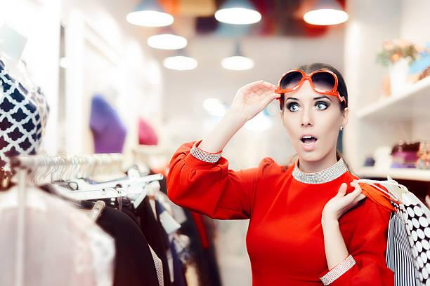 surprised elegant woman shopping in fashion store - kleider günstig kaufen stock-fotos und bilder