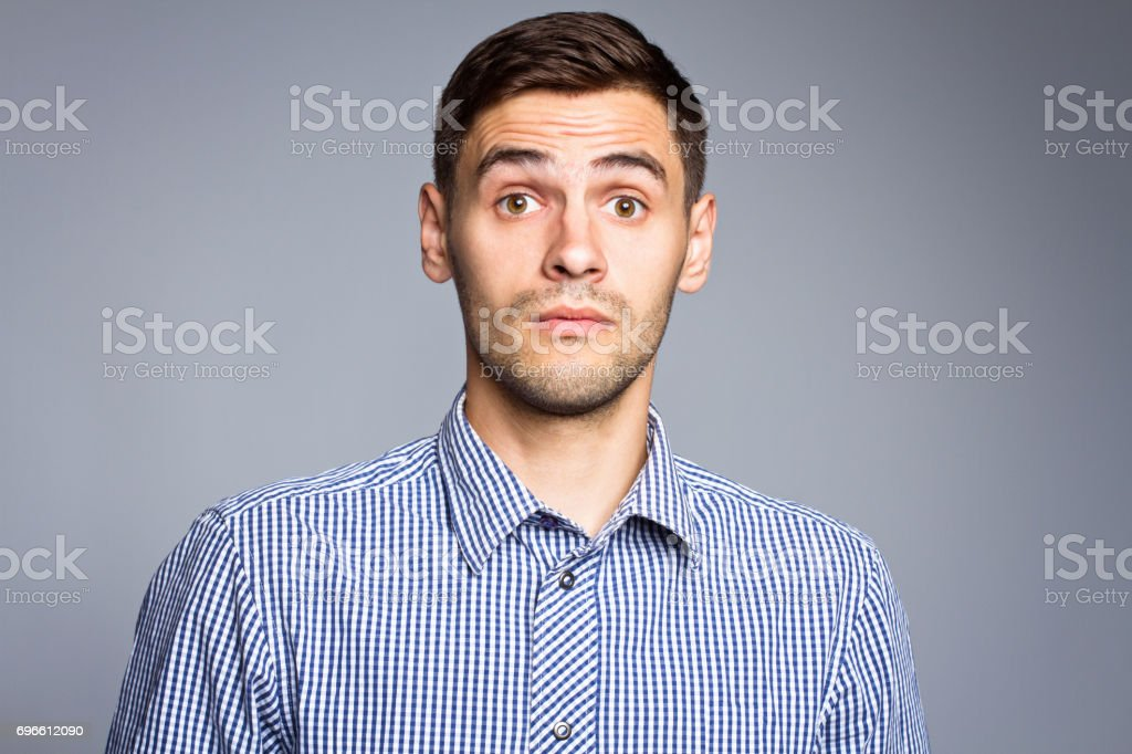 Surprised face of business man on gray background stock photo