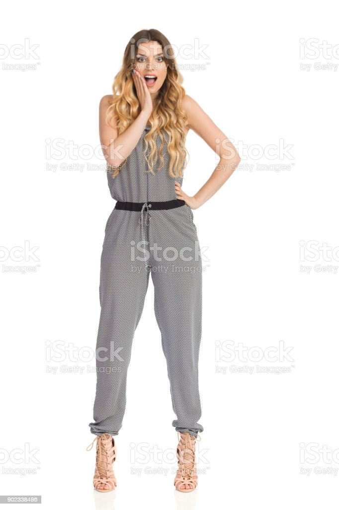 Surprised Fashion Model In Jumpsuit And High Heels Is Standing And Holding Hand On Chin stock photo
