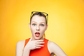Surprised fashionable young  woman in orange dress