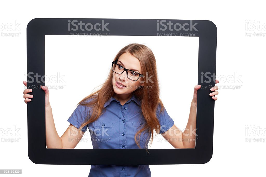 Surprised female peeping out of tablet frame stock photo