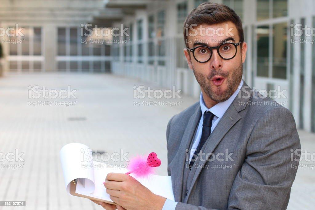 Surprised flamboyant businessman taking notes stock photo