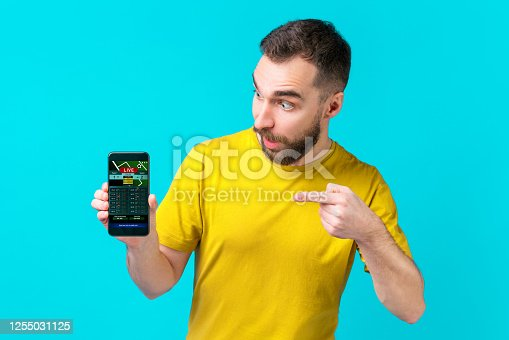 1032204252 istock photo Surprised football fan pointing with his index finger at the smartphone screen with bookmaker's website interface template 1255031125