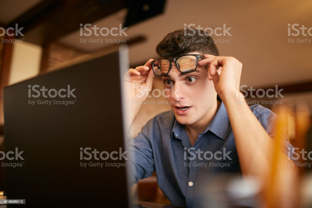 Surprised freelancer hipster man looks to laptop screen and can not believe he won lottery prize or green card visa. Pop-eyed successfull amazed businessman trader raises one's glasses above his eyes stock photo