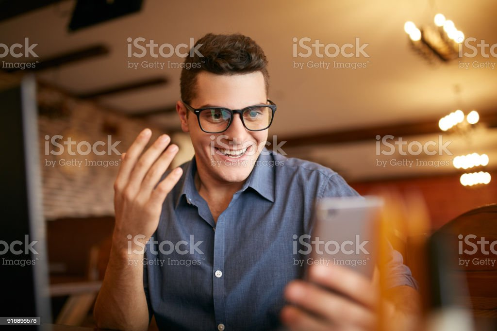 Surprised freelancer hipster man looks to smartphone and can not believe he won lottery prize or money in trading cryptocurrency. Pop-eyed successfull amazed businessman trader. Video call conference stock photo