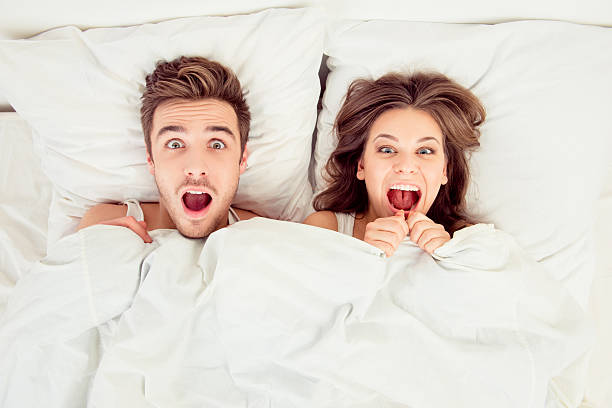 Surprised funny couple in love lying in the bed stock photo