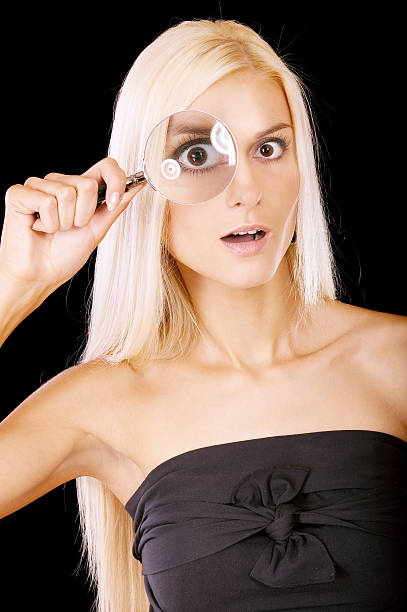 Surprised girl looks in a magnifier stock photo