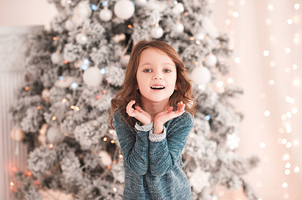 surprised girl over christmas tree - festliche babymode junge stock-fotos und bilder