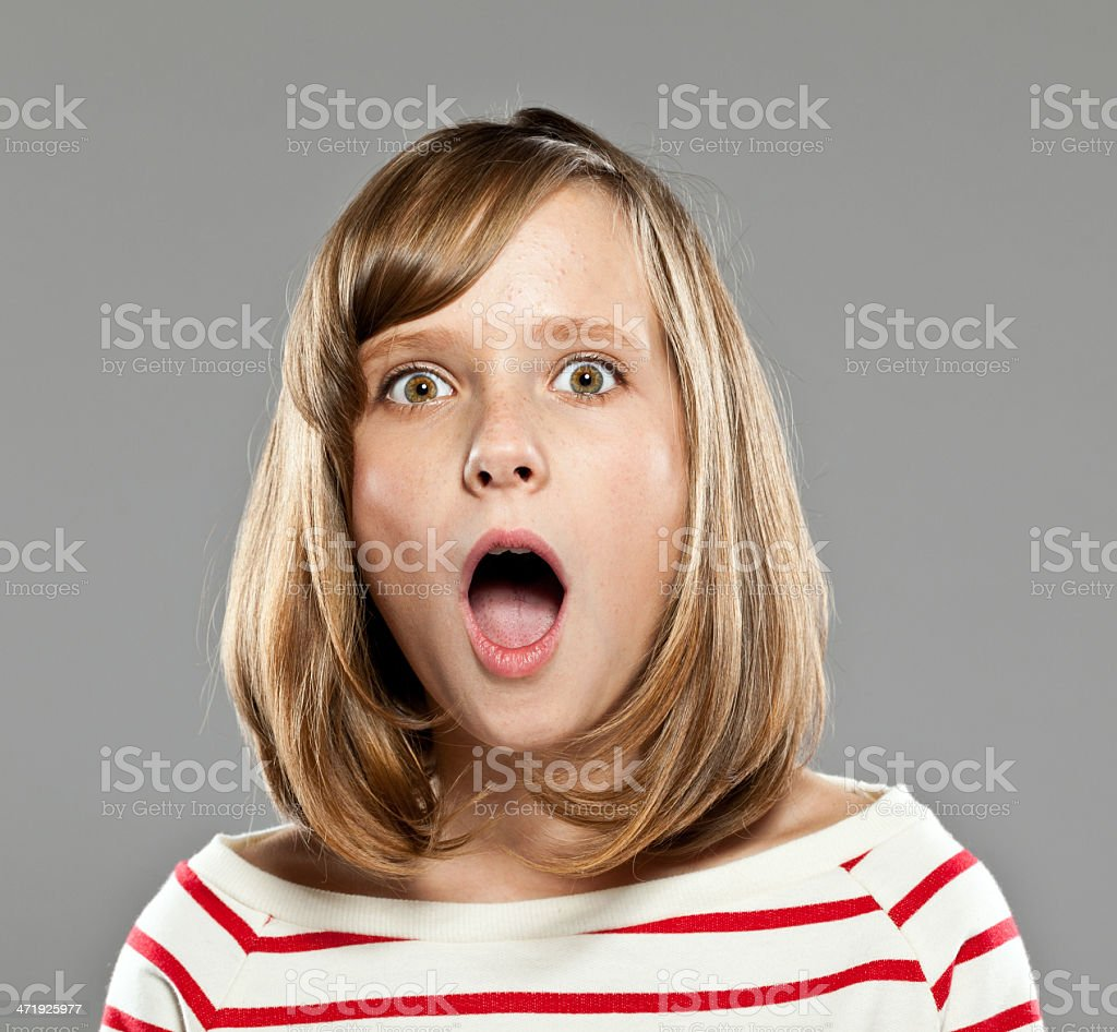 Surprised girl Portrait of surprised girl wearing striped blouse staring at camera, Studio shot. 10-11 Years Stock Photo