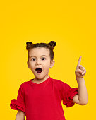 Curious little child in red clothing looking at camera with surprised face expression and pointing up against bright yellow background
